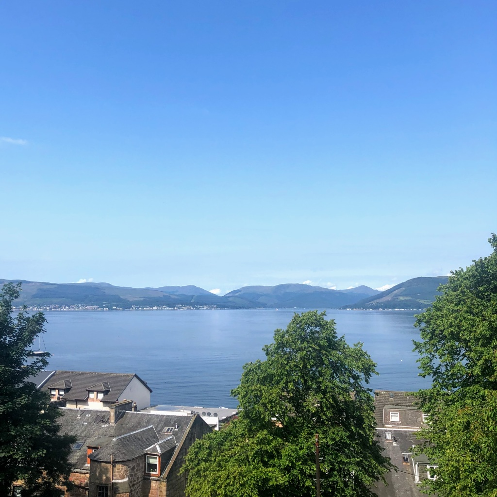 View across the Firth of Clyde from Gourock: nearly-cloudless skies above the hills and the river, with roofs and trees in hte foreground.